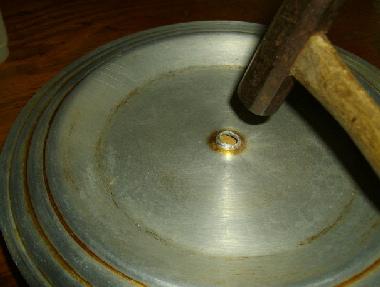 鍋の裏に木片を置き、ハンマーで叩いて直す